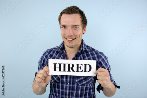 young man holding hired sign