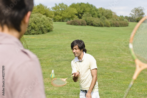 Friends playing badminton in park