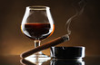 glass of brandy and cigar on brown background