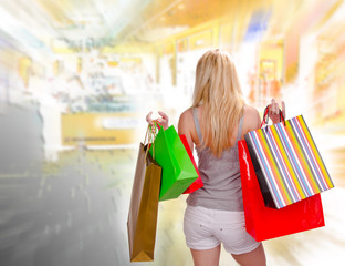 Blond girl with shopping bags, backview