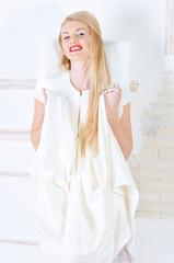 beautiful young woman in white dress posing