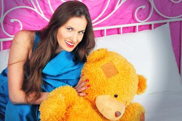 beautiful young woman on a bed with teddy bear