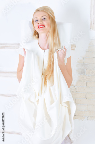 beautiful young woman in white dress posing