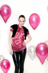 frau in pink mit vielen schwebenden luftballons