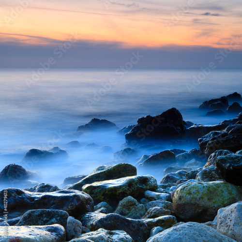 Seashore with misty water at sunset © Aleksey Sagitov