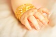 Baby hand with yellow gold bracelets, towards silk