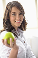 Young woman holding green apple in hand, portrait