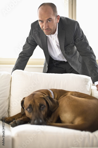Businessman standing behind dog, portrait