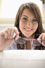 Young woman holding spectacles, smiling, portrait