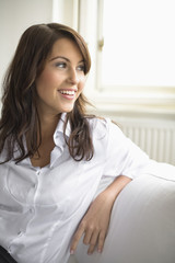 Young woman sitting on sofa, smiling