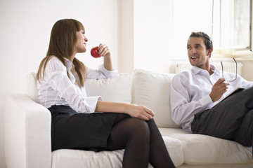 Mid adult couple conversing on sofa, side view