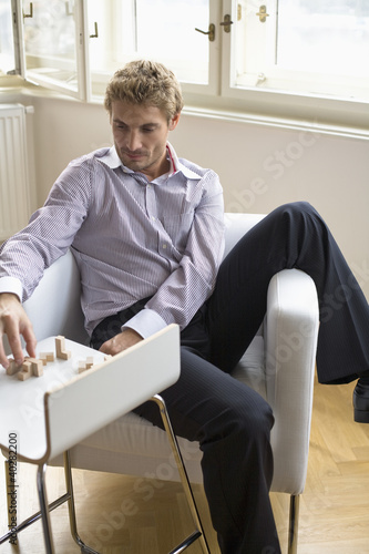 Mid adult man arranging wooden blocks