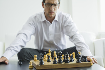 Mid adult man looking at chess board