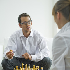 Mid adult couple playing chess, side view