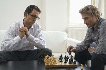 Mid adult men playing chess