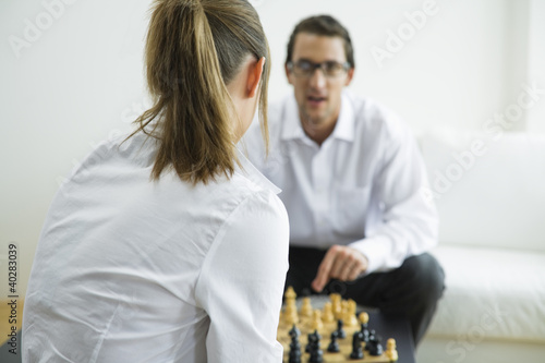 Mid adult couple playing chess