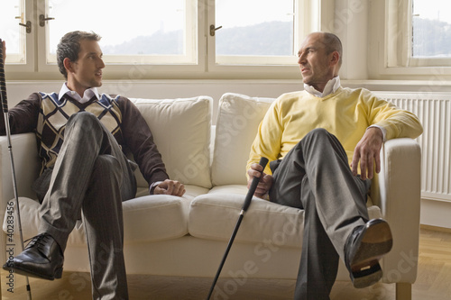 Men holding golf clubs, conversing