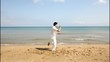 Man practicing Tai Chi  on the beach