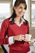 Businesswoman holding teacup, smiling, portrait