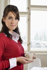 Businesswoman holding teacup, portrait