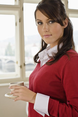 Businesswoman holding teacup, portrait