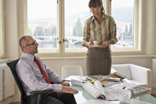 Businesswoman holding cup while businessman sitting on chair