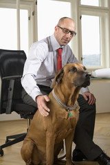 Businessman sitting on chair with dog in office