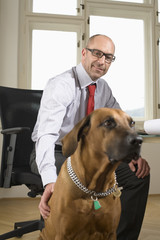 Businessman sitting on chair with dog in office, low angle view