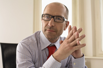 Businessman sitting with hands clasped in office, portrait