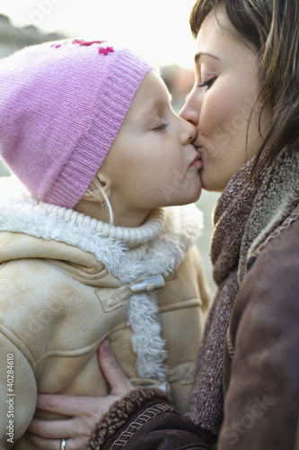 Mother kissing daughter, side view, close-up