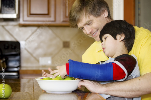 Father helping disabled son with work in the kitchen