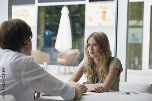 Young couple sitting at cafe, side view