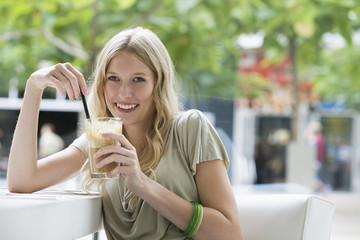 Young woman holding glass of coffee