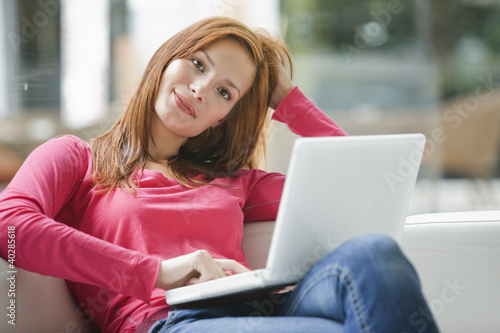 Young woman using laptop, portrait