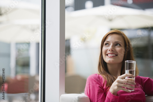 Young woman holding glass of water, looking up