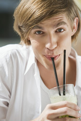 Young man holding glass of cocktail, portrait, close-up