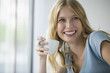 Young woman holding coffee cup, smiling