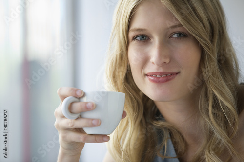 Young woman holding coffee cup, portrait