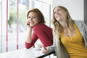 Young women leaning on window sill, smiling