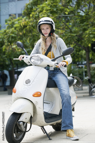 Young woman sitting on motor scooter