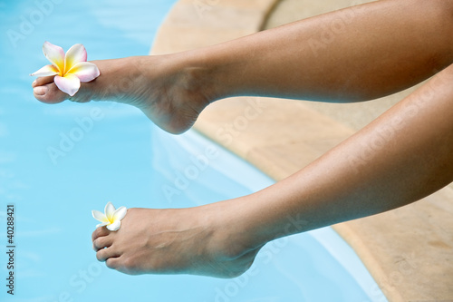 female foot with a flower over blue water....