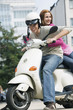 Young couple sitting on motor scooter, smiling