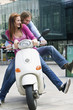 Young couples sitting on motor scooter, smiling