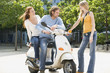 Young couple on motor scooter, talking to friend