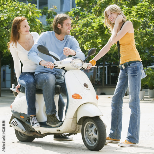 Young couple sitting on motor scooter while friend smiling