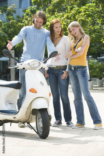 Friends looking at motor scooter, smiling