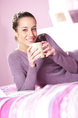 woman holding a cup of coffee in bed