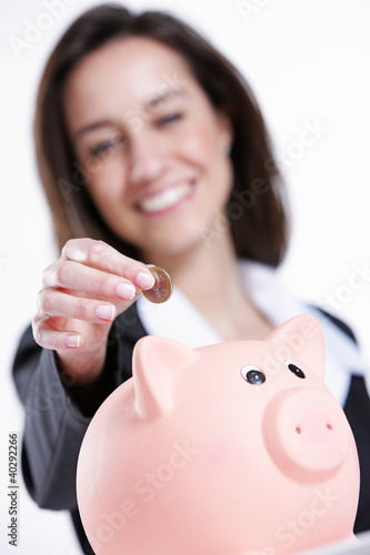 Close-up of young woman putting coin into a piggy bank