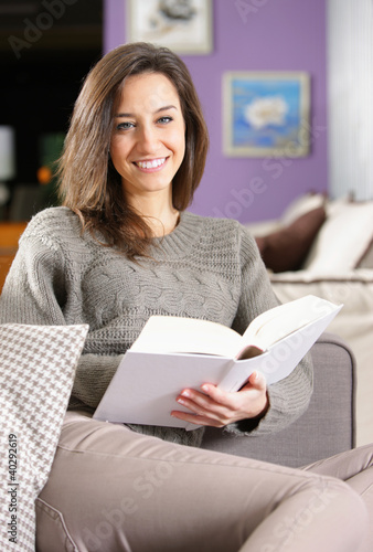 young woman lying on couch with book