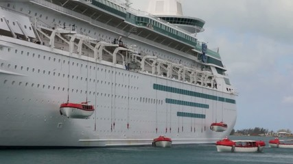 Modern cruise ship deploying lifeboats during a safety drill